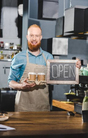 young male barista holding chalkboard with lettering open and two papers cups of coffee
