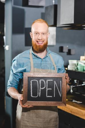 smiling young male barista holding chalkboard with lettering open in coffee shop