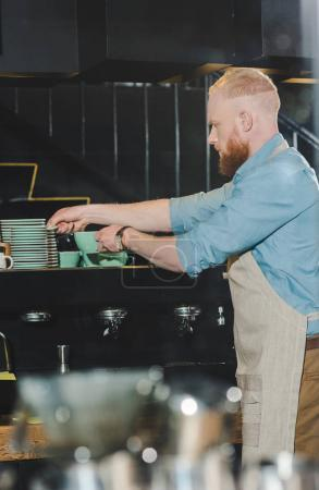 side view of young male barista taking saucer for coffee mug