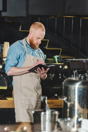 side view of young male barista in apron writing in textbook