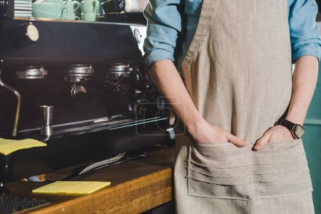 Photo for Cropped image of male barista in apron standing near coffee machine - Royalty Free Image