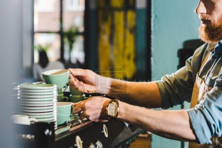 cropped image of young male barista in apron taking mugs in coffee shop