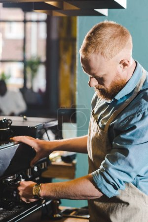 young bearded male barista in apron using coffee machine