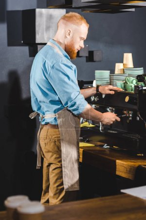 young male barista in apron using coffee machine