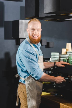 smiling young male barista doing coffee on machine in coffee shop