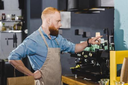 Photo pour Jeune mâle barista en tablier prenant commande sur tablette numérique - image libre de droit