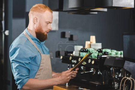 side view of young male barista looking at menu in coffee shop