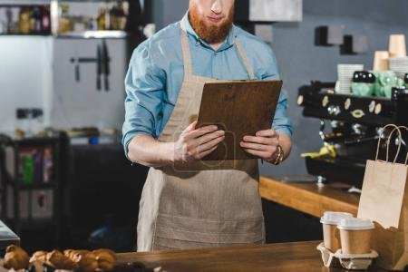 cropped shot of serious young bearded barista holding clipboard in coffee shop