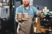 photo recadrée de barista barbu souriant, tenant des tasses à café jetables et sac en papier dans le café