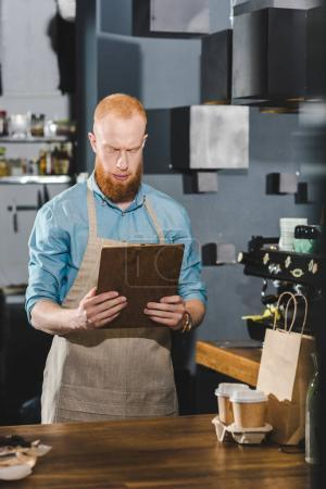 serious bearded barista in apron holding clipboard while working in coffee shop
