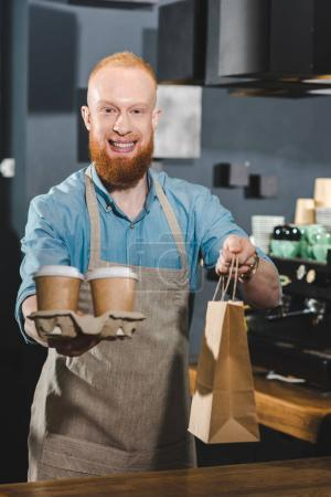 smiling bearded barista holding paper bag and disposable coffee cups