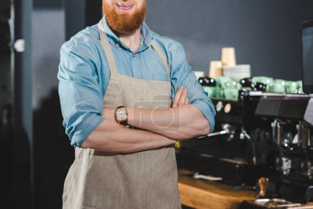 cropped shot of smiling bearded barista in apron standing with crossed arms in coffee shop