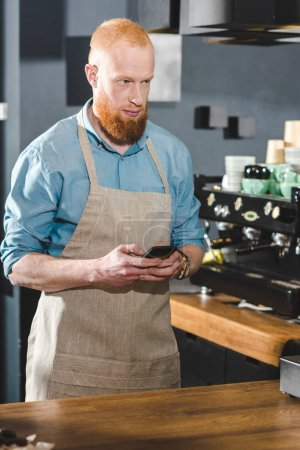 bearded young barista in apron using smartphone and looking away in coffee shop