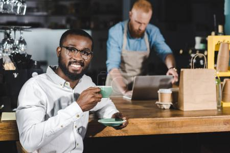 handsome young african american man drinking coffee and smiling at camera while bartender using laptop behind