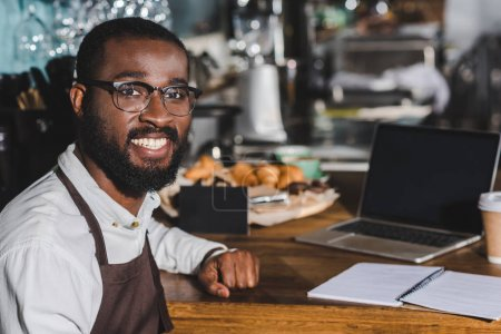 handsome young african american barista in eyeglasses smiling at camera while working in cafe