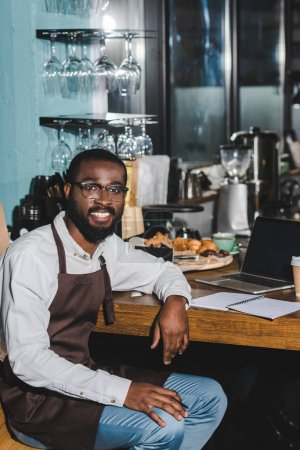 handsome young african american barista in eyeglasses smiling at camera while working with laptop in coffee shop