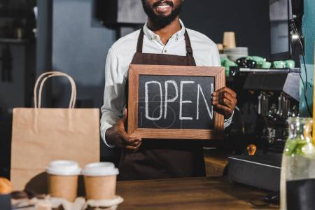 cropped shot of smiling african american barista holding sign open in coffee shop