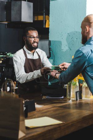 cropped shot of cheerful african american barista giving cup of coffee to bearded young client in cafe