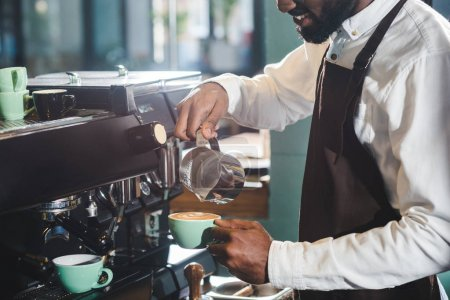 cropped shot of smiling african american barista making cappuccino at coffee machine