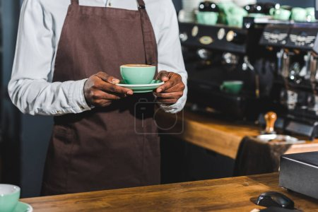 cropped shot of african american barista holding cup of cappuccino in coffee shop