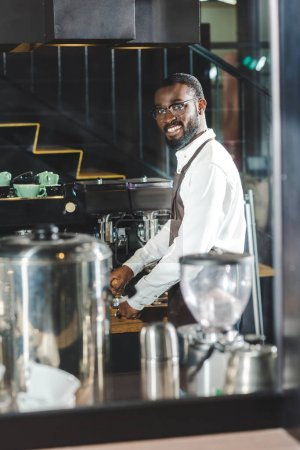 handsome young african american barista in eyeglasses smiling at camera while making coffee at coffee machine