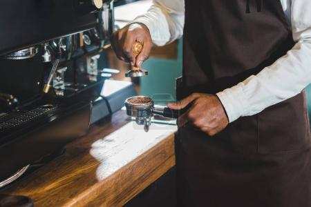 cropped shot of african american barista in apron making coffee at coffee machine