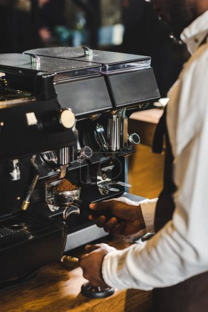 cropped shot of african american barista in apron preparing coffee at coffee machine