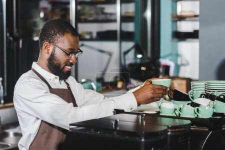 happy young african american barista in eyeglasses arranging cups on top of coffee machine