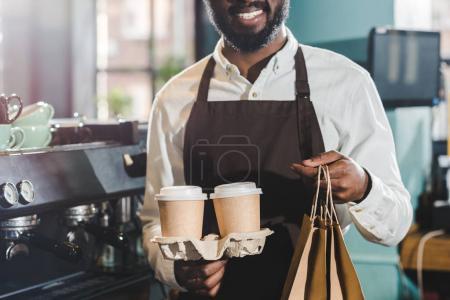 Foto de Recortar el tiro de sonreír afroamericano barista con bolsas de papel y tazas de café desechables en la cafetería - Imagen libre de derechos