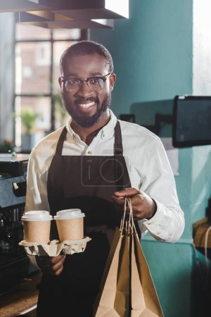 cheerful young african american barista holding paper cups and bags in coffee shop