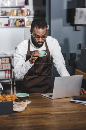 young african american barista holding cup of coffee and using laptop in cafe
