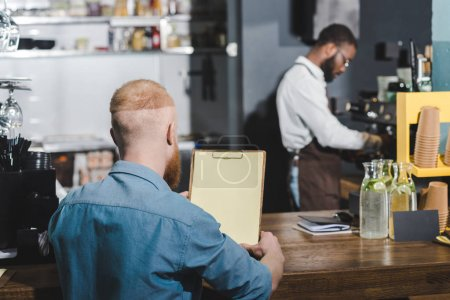 rear view of young man holding blank clipboard while barista making coffee behind