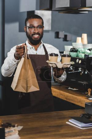 handsome smiling young african american barista holding disposable coffee cups and paper bags in coffee shop