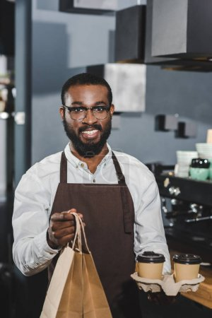 young african american barista holding disposable coffee cups and paper bags, smiling at camera in coffee shop