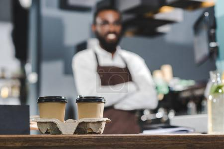 close-up view of two paper cups with coffee and smiling african american barista standing with crossed arms behind