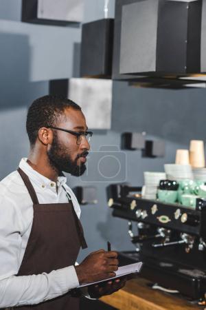 Photo pour Vue du côté des jeune afro-américains barista en lunettes, prendre des notes alors qu'il travaillait dans le café-restaurant - image libre de droit
