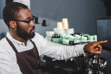 young african american barista in eyeglasses pointing at screen while working at coffee shop