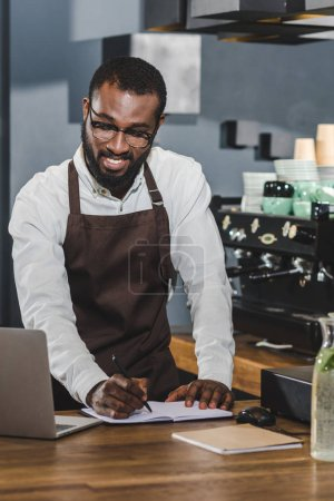 smiling young african american barista taking notes and using laptop at coffee shop