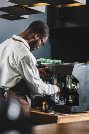 young african american barista in eyeglasses and apron working with coffee machine