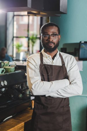 handsome african american barista standing with crossed arms and looking at camera in coffee shop