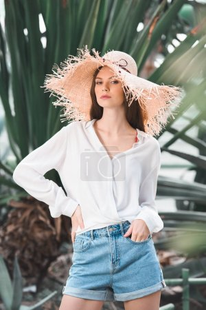 beautiful woman in summer blouse and straw hat posing in tropical garden