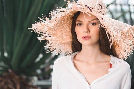 attractive girl in straw hat posing in tropical garden