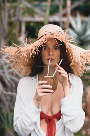 beautiful girl in straw hat drinking coconut cocktail
