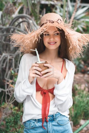 attractive woman in summer outfit and straw hat posing with fresh coconut cocktail