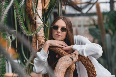 beautiful girl in trendy sunglasses posing in tropical garden
