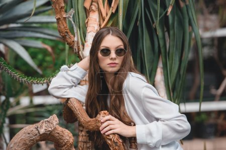 stylish girl in trendy sunglasses posing in tropical garden in summer