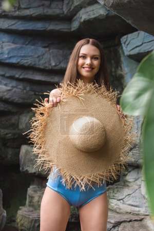 beautiful smiling woman in straw hat in tropical garden