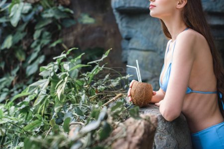 cropped view of girl posing with coconut cocktail in tropical garden