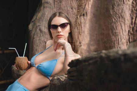attractive girl in sunglasses posing with coconut cocktail