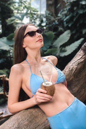 beautiful girl in sunglasses posing with coconut cocktail in tropical garden